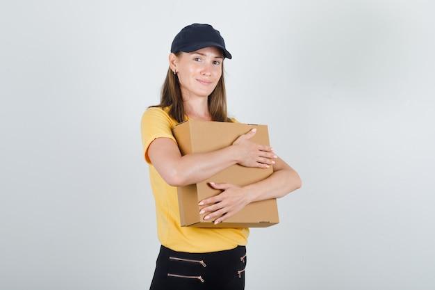 Levering vrouw kartonnen doos knuffelen in t-shirt, broek, pet en op zoek blij.