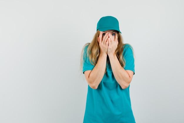 Levering vrouw kijkt door vingers in t-shirt, pet en kijkt bang.