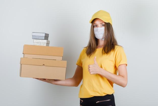 Levering vrouw met dozen met duim omhoog in t-shirt, broek en pet, masker en op zoek vrolijk