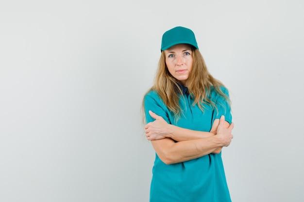 Levering vrouw met gekruiste armen in t-shirt, pet en op zoek zelfverzekerd.