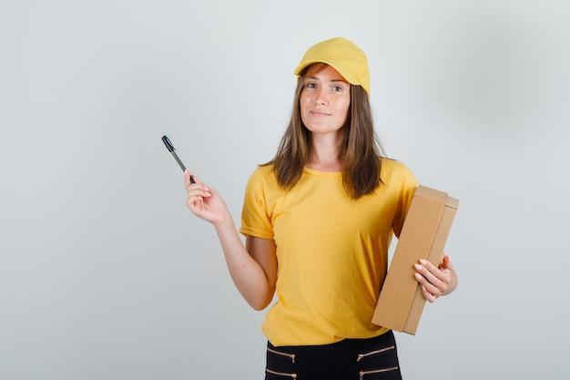 Levering vrouw met kartonnen doos en pen in t-shirt, broek en pet en op zoek blij