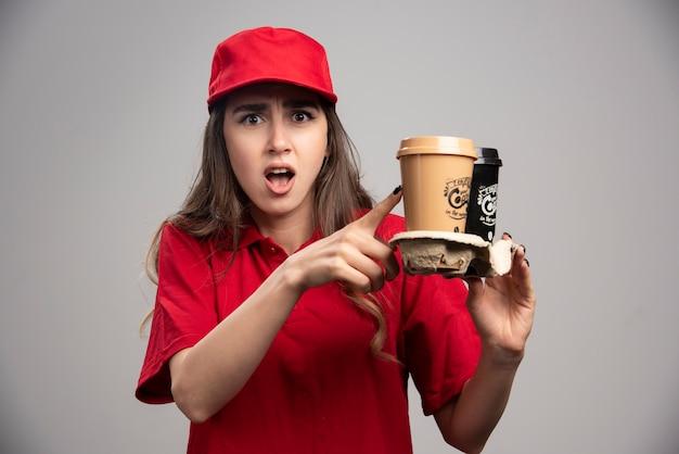 Levering vrouw met koffiekopjes op grijze muur.