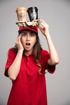 Levering vrouw met koffiekopjes op haar hoofd.