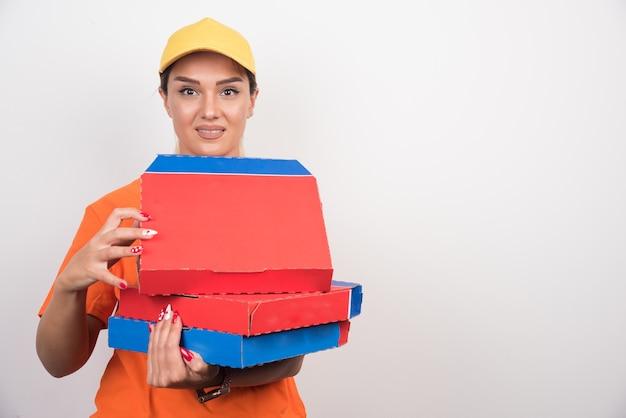Levering vrouw met pizzadozen op witte ruimte