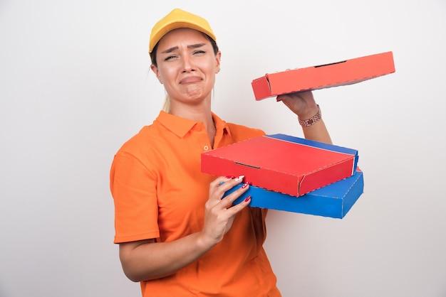Levering vrouw met verveelde uitdrukking pizzadozen op witte ruimte te houden