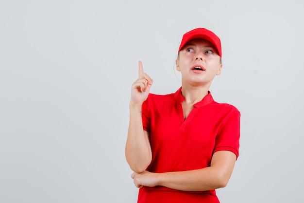 Levering vrouw omhoog in rood t-shirt en pet en nieuwsgierig kijken