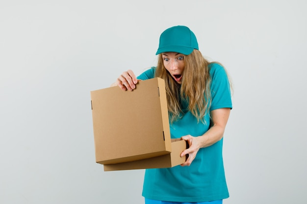 Levering vrouw op zoek naar kartonnen doos in t-shirt, pet en vraagt zich af.