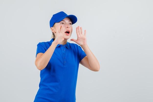 Levering vrouw schreeuwen of iets aankondigen in blauw t-shirt en pet