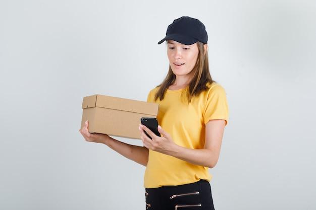 Levering vrouw smartphone met kartonnen doos in t-shirt, broek en pet kijken.