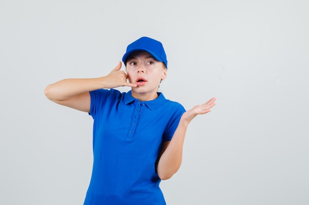 Levering vrouw telefoongebaar met gespreide palm in blauw t-shirt en pet tonen