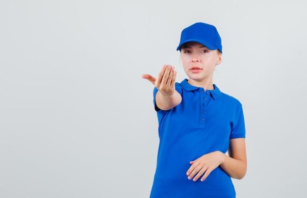 Levering vrouw uitnodigend om te komen in blauw t-shirt en pet