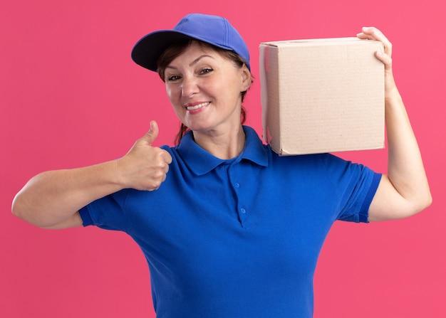 Levering vrouw van middelbare leeftijd in blauw uniform en pet met kartonnen doos op haar schouder met duimen omhoog glimlachend vrolijk staande over roze muur