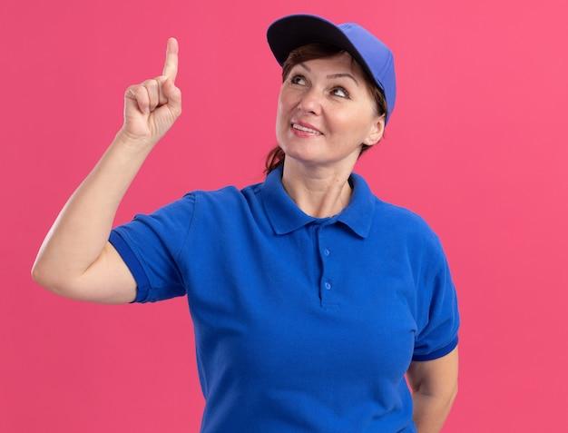 Levering vrouw van middelbare leeftijd in blauw uniform en pet opzoeken met glimlach op gezicht wijzend met wijsvinger naar iets staande over roze muur