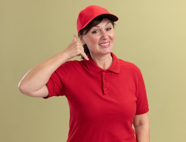 Levering vrouw van middelbare leeftijd in rood uniform en pet kijken naar voorkant lachend bel me gebaar staande over groene muur