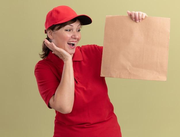 Levering vrouw van middelbare leeftijd in rood uniform en pet met papieren pakket kijkend naar het blij en opgewonden staande over groene muur Gratis Foto