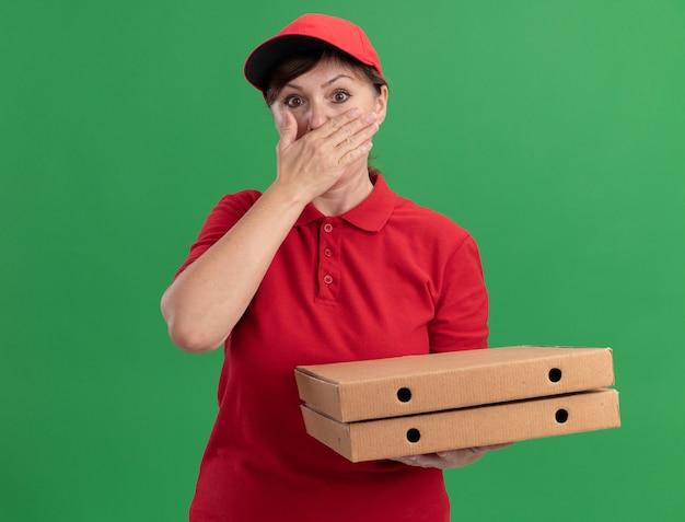 Levering vrouw van middelbare leeftijd in rood uniform en pet met pizzadozen die voorzijde bekijken die geschokt worden die mond bedekken met hand die zich over groene muur bevindt