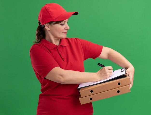 Levering vrouw van middelbare leeftijd in rood uniform en pet met pizzadozen en klembord met blanco pagina's die met ernstig gezicht schrijven dat zich over groene muur bevindt