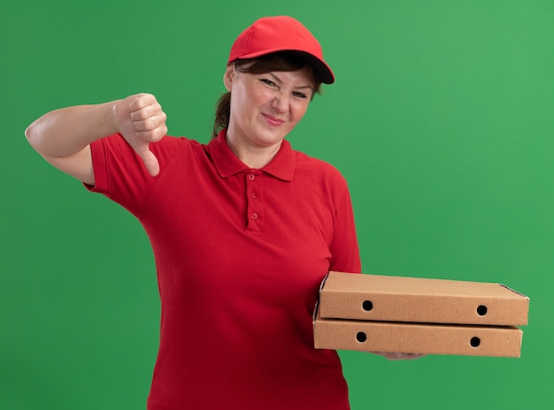 Levering vrouw van middelbare leeftijd in rood uniform en pet met pizzadozen kijken naar voorkant verward tonen duimen neer staande over groene muur