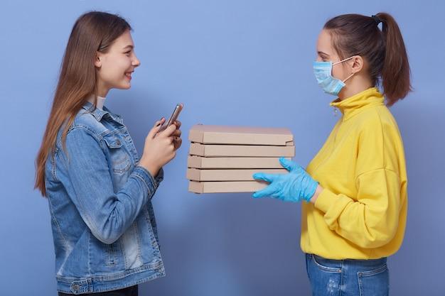 Levering vrouw werknemer in geel overhemd, masker en handschoenen