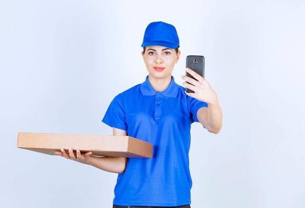 Levering vrouw werknemer in uniform met ambachtelijke papieren doos met mobiele telefoon.