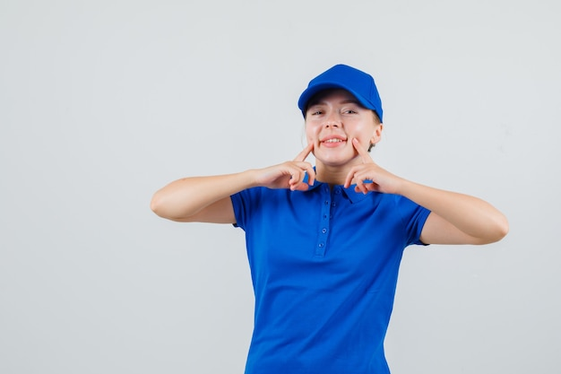 Levering vrouw wijst naar haar kuiltjes in blauw t-shirt en pet en ziet er vrolijk uit