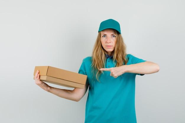 Levering vrouw wijzend op kartonnen doos in t-shirt, pet