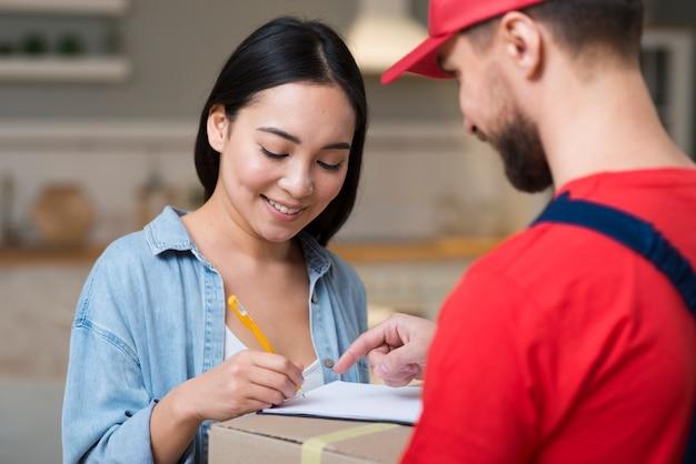 Levering wacht op vrouw om te ondertekenen om haar bestelling te ontvangen