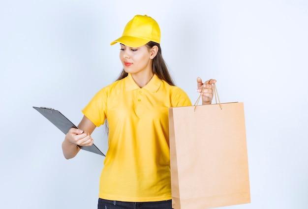 Levering werknemer vrouw in gele dop in de hand houden bruin ambachtelijk papier en klembord.