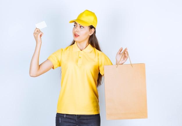 Levering werknemer vrouw in gele dop met ambachtelijke tas en visitekaartje.