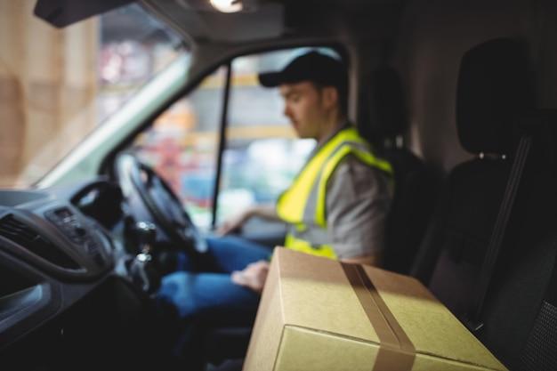 Leveringsbestuurdersbestuurwagen met pakketten op zetel buiten pakhuis