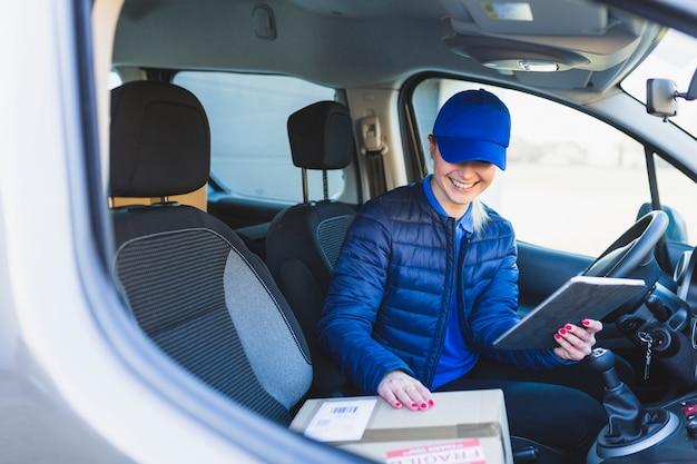 Leveringsmeisje met tablet in auto