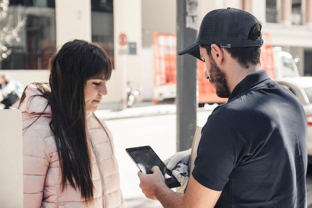 Leveringsmens die digitale tablet gebruiken dichtbij vrouwelijke klant