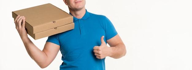 Leveringsmens die duimen tonen terwijl het dragen van pizzadozen