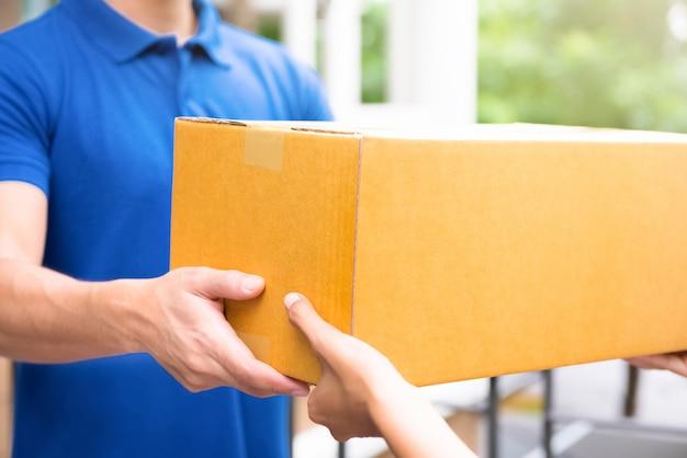 Leveringsmens die in blauwe eenvormig pakketdozen overhandigen aan ontvanger