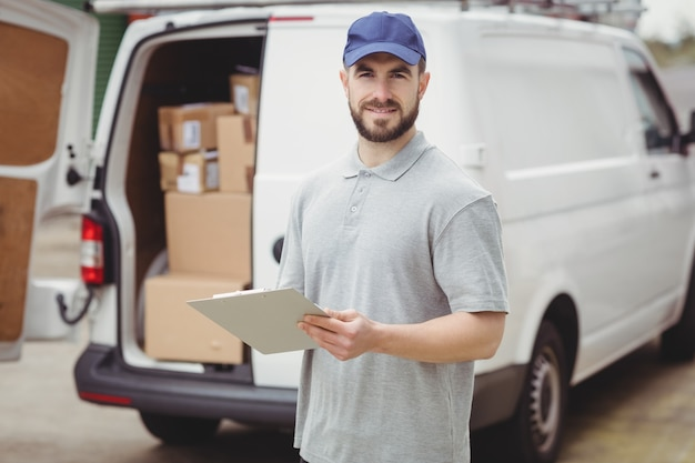 Leveringsmens die op klembord voor zijn bestelwagen schrijven