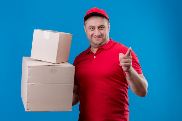 Leveringsmens die rode eenvormig dragen en glb-de dozen die van het holdingskarton aan iets met wijsvinger richten die het zekere en gelukkige glimlachen over blauwe muur kijken