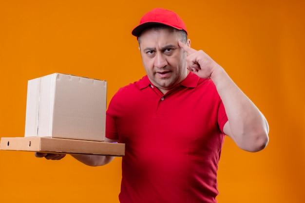 Leveringsmens die rode eenvormig dragen en glb-de dozen die van het holdingskarton tempel met vinger richten die zich hard op een idee over oranje muur concentreren