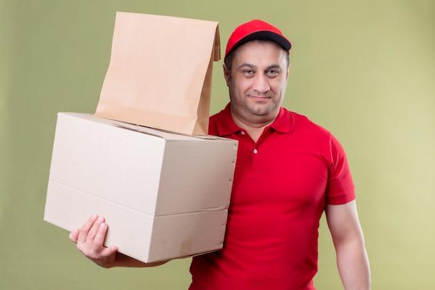 Leveringsmens die rode eenvormig en glb-kartondozen dragen die zeker het glimlachen over geïsoleerde groene muur kijken