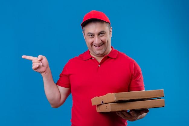 Leveringsmens die rode eenvormig en glb-pizzadozen dragen die met gelukkig gezicht glimlachen die met wijsvinger aan de kant over blauwe muur richten
