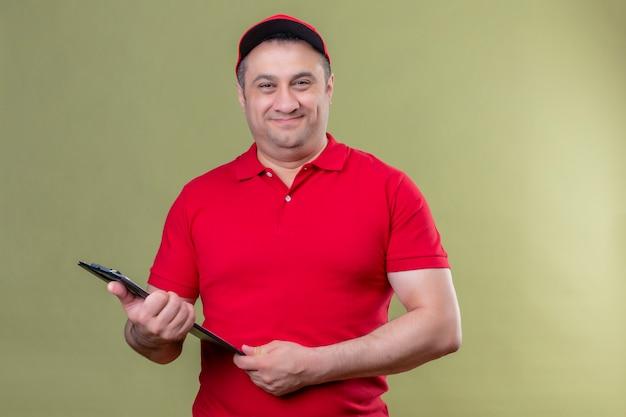 Leveringsmens die rood eenvormig en glb-holdingsklembord dragen die positief en het gelukkige glimlachen over geïsoleerde groene muur kijken