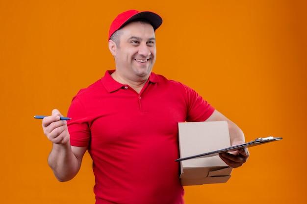 Leveringsmens die rood uniform en glb-het pakket en de klembord van de holdingsdoos met pen dragen die opzij met gelukkig gezicht kijken die over oranje muur glimlachen