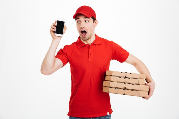 Leveringsmens in rode eenvormige holdingsstapel pizzadozen en holdingscel terwijl het hebben van vraag, die over witte ruimte wordt geïsoleerd