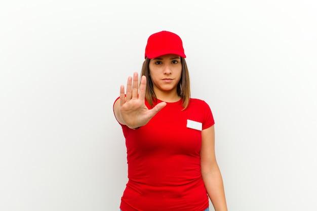 Leveringsvrouw die ernstig, streng, ontevreden en boos tonen die open palm tonen die eindegebaar maken tegen wit