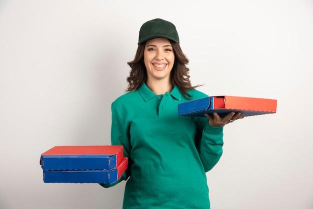 Leveringsvrouw die lacht terwijl ze pizza vasthoudt.