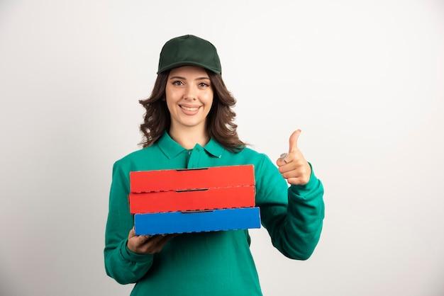 Leveringsvrouw die met pizzadozen duimen opgeven.