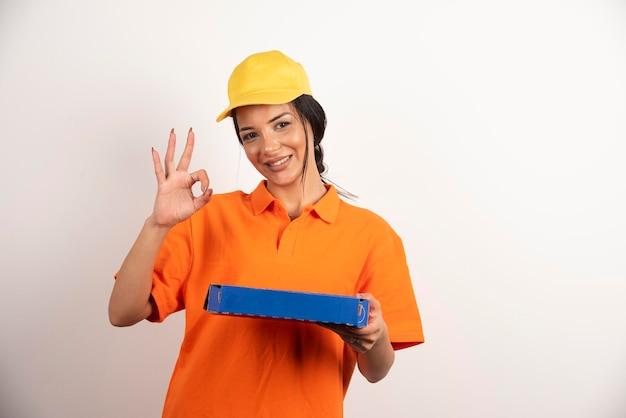 Leveringsvrouw die pizza houdt en ok gebaar op witte muur toont.