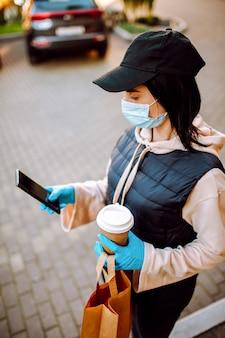 Leveringsvrouw in beschermend gezichtsmasker en handschoenen met een zak voedsel en koffie die adressen met haar smartphone controleren