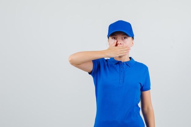 Leveringsvrouw in blauw t-shirt en glb die hand op mond houden en ernstig kijken
