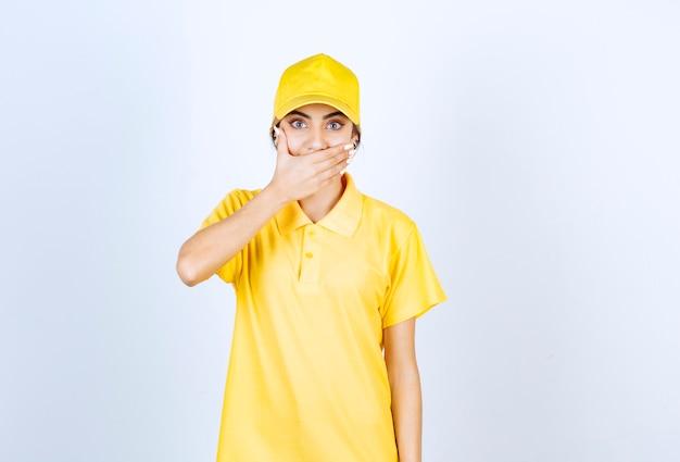 Leveringsvrouw in geel uniform die mond bedekt met hand.
