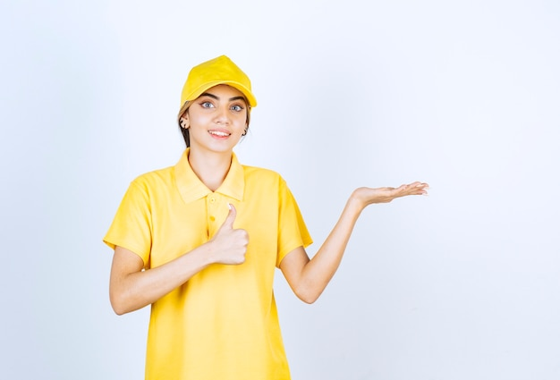 Leveringsvrouw in geel uniform staand en geopende handpalm.